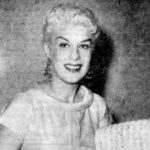 Posed photograph of a white woman with blonde hair holding sheet music