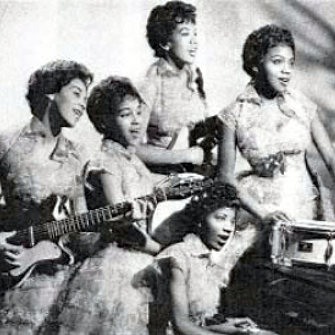 five young african american women in matching dresses, some are playing instruments (guitar, piano, and a drum)