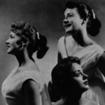 Three young white women wearing matching dresses in a posed studio shot.