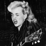 A young blonde woman with a guitar. Here eyes are closed and she appears to be singing loudly,