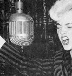 A young woman with blond hair sings into an old fashioned microphone with her eyes shut, as if she is singing loudly