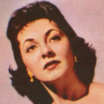 An old color photo of a white woman with dark hair gazing into the middle distance