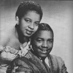 An African American couple posed in a studio photograph in semi-formal attire