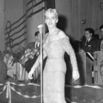 A young blonde woman in a tight dress sings in front of a bandstand