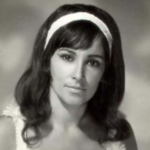 A young woman with long dark hair wearing a headband