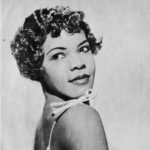 A young African American woman in a formal 3/4 view posed headshot photograph